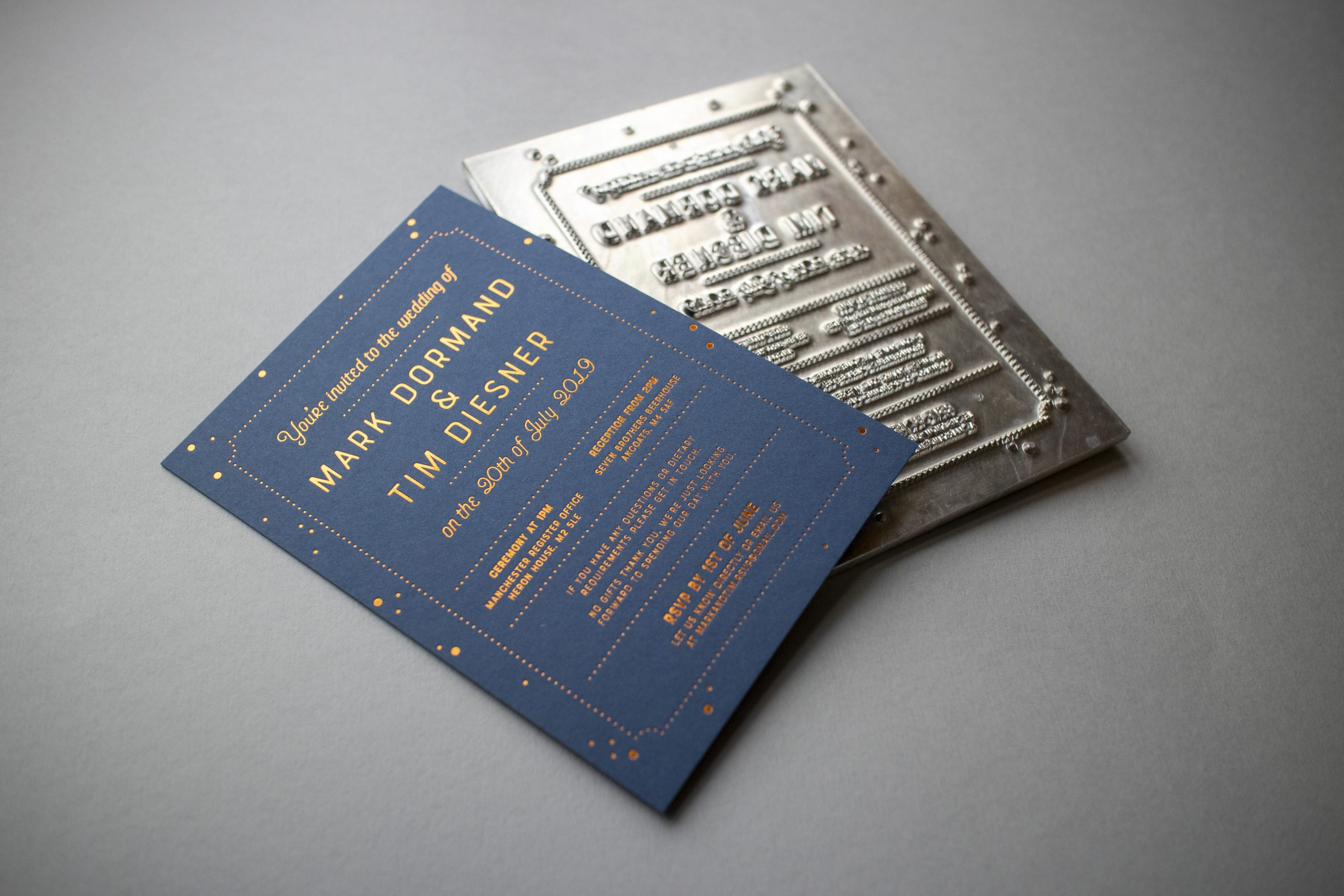 Photograph of a wedding invite, an A6 thick card of Cobalt colorplan hot foil pressed with copper foil. Behind the card is the metal plate used to imprint the invites
