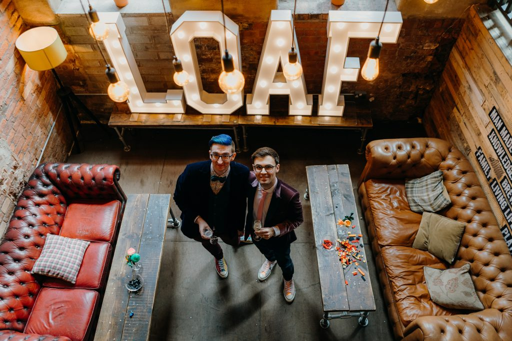 Photograph of Mark and Tim on their wedding day in front of huge letters which spell out LOAF as a play on LOVE.