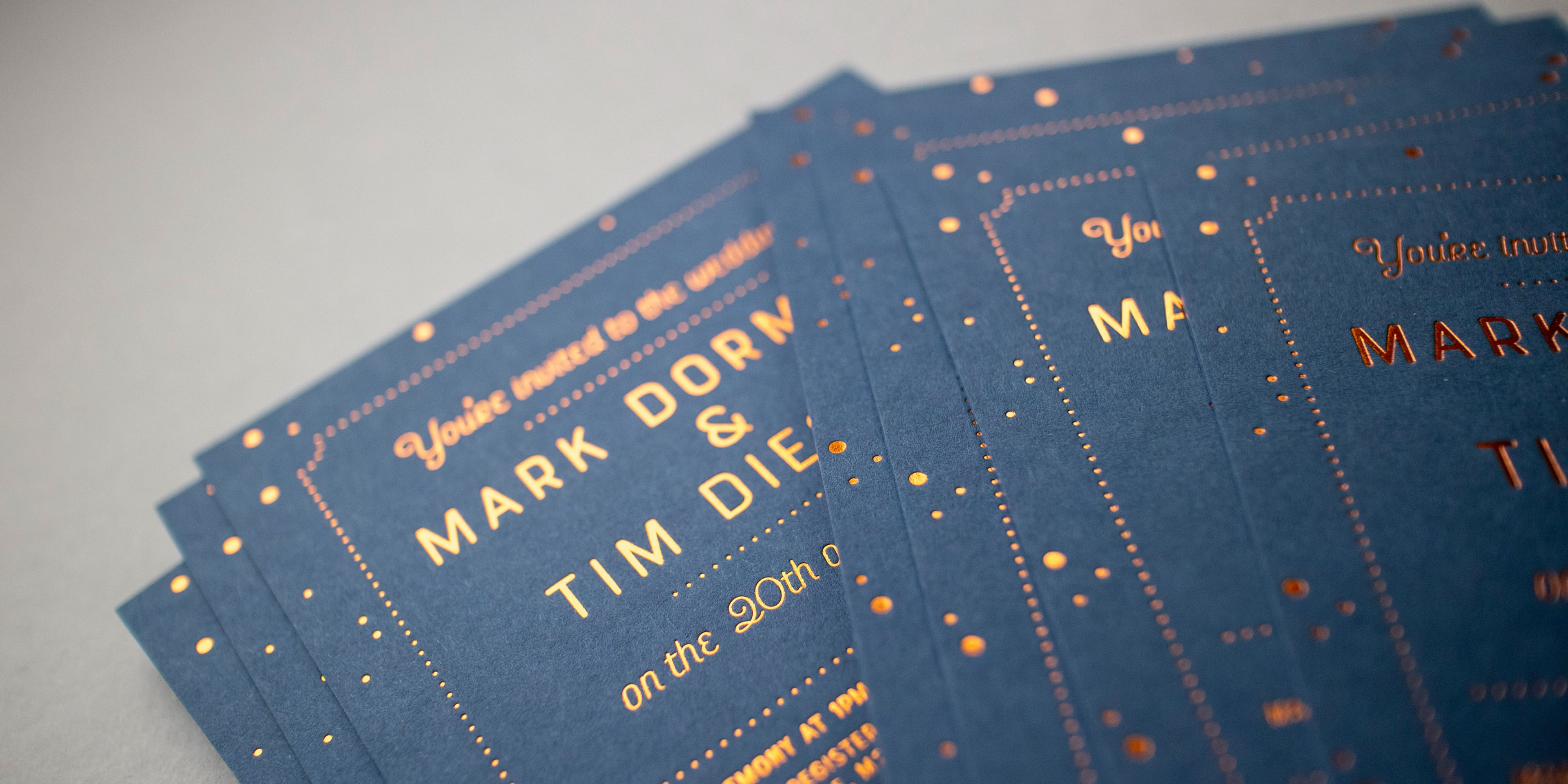 A close up photograph of Mark and Tim's wedding invites showing the detail of the copper foil pressed into the cobalt blue cards. The style is slightly vintage, with thin condensed sans serif type, surrounded by a border of simple star patterns.