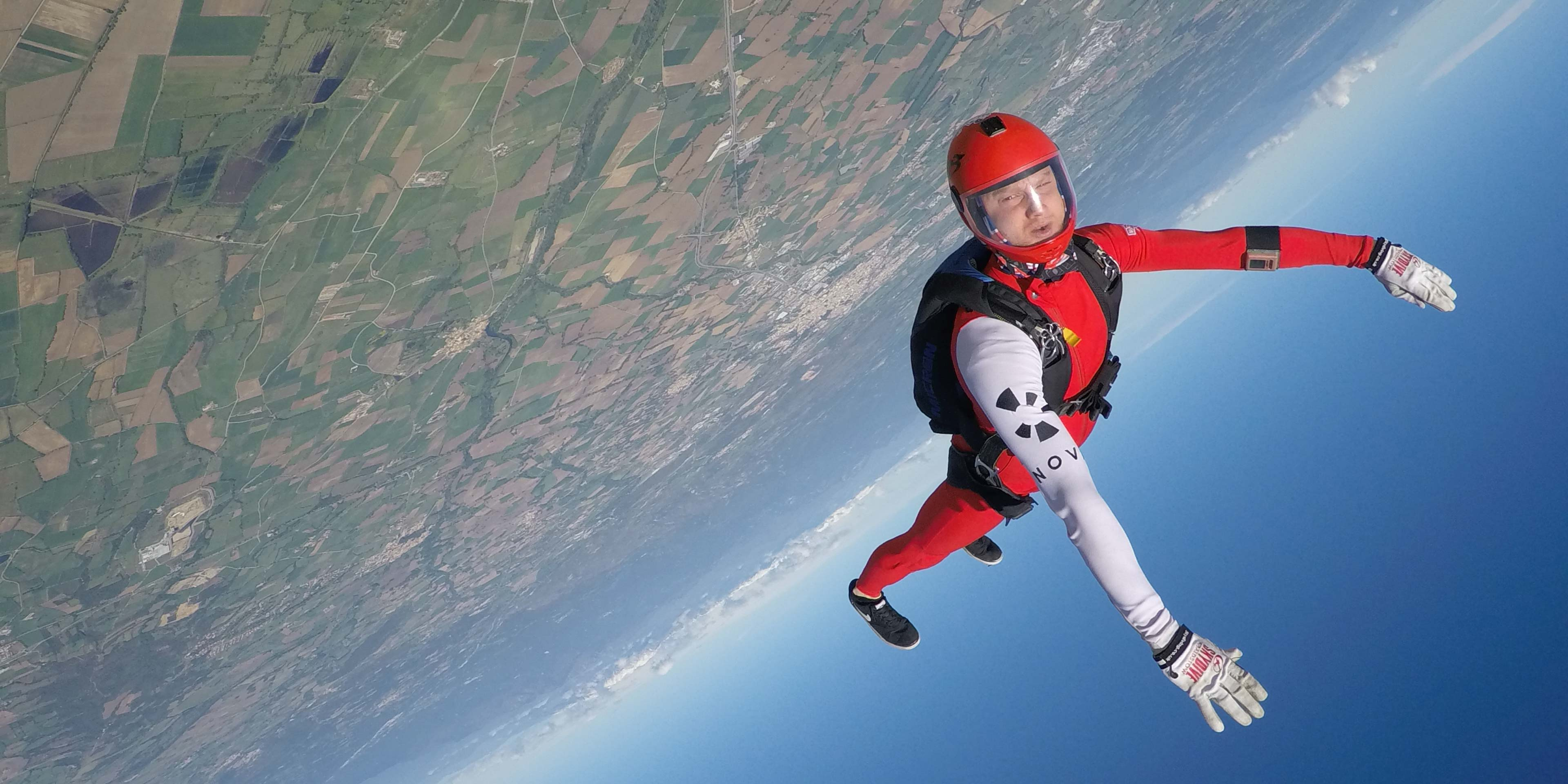 Photograph of a skydiver falling through the sky with a red and white suit on. A black version of the Nova logo is on the sleeve.
