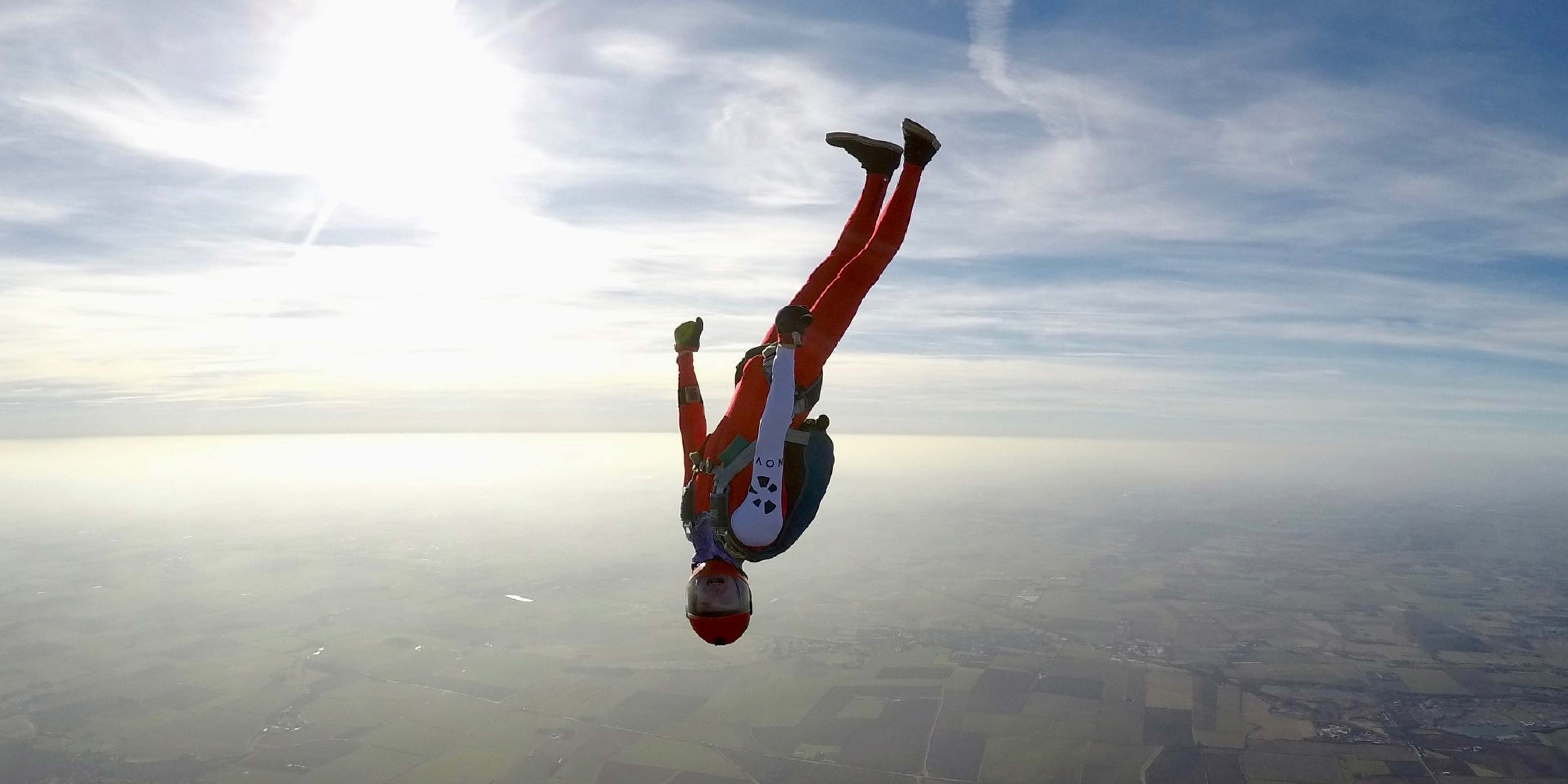 A photograph of a skydiver falling through the sky in another position, the logo is visible in black on white on his arm.
